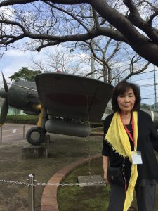 Kay in Japan standing beside WWII airplane